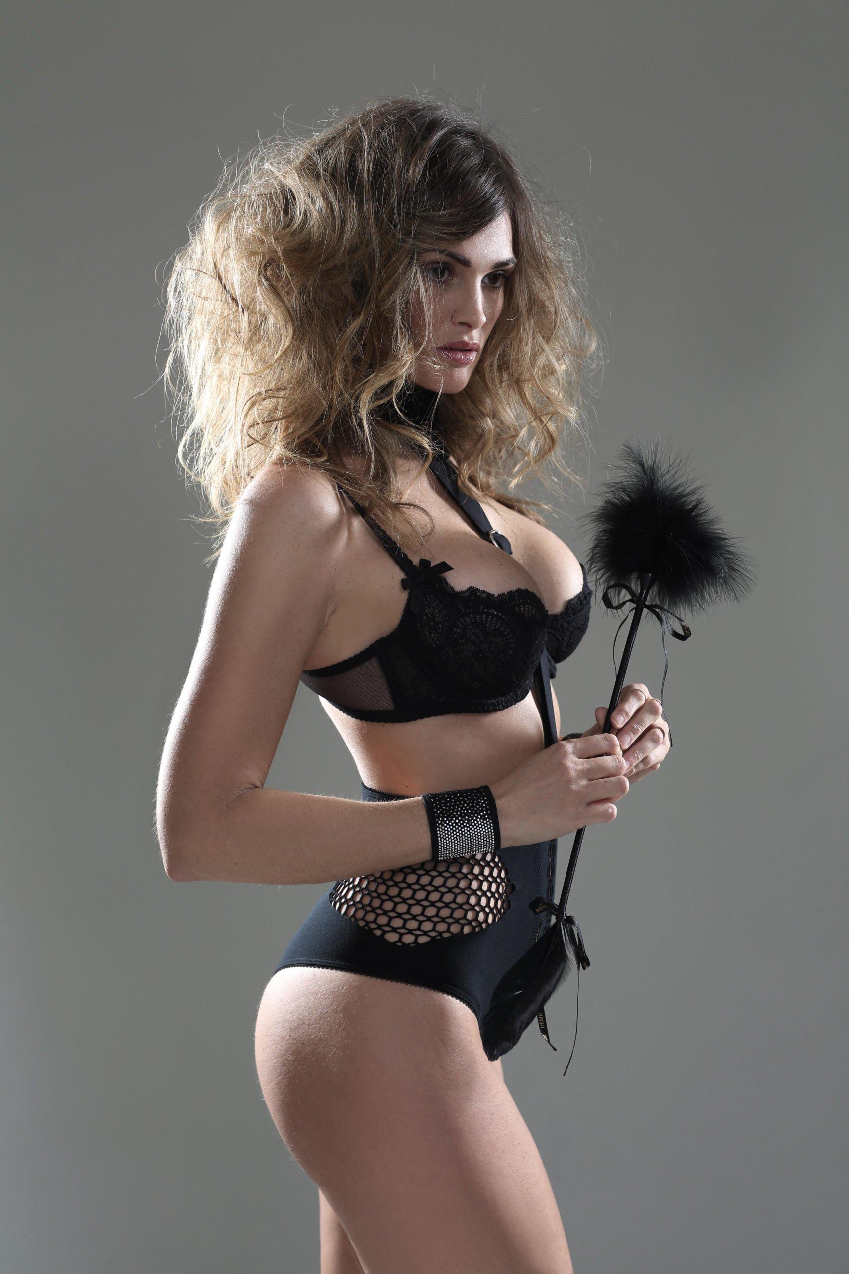Brunette boudoir model in black bra history of boudoir photography by Caroline Malouf