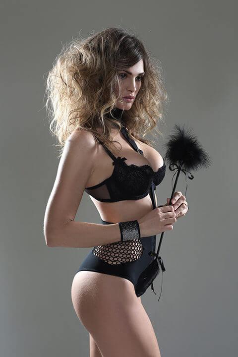 Brunette boudoir model in black bra carrying a feather tickler
