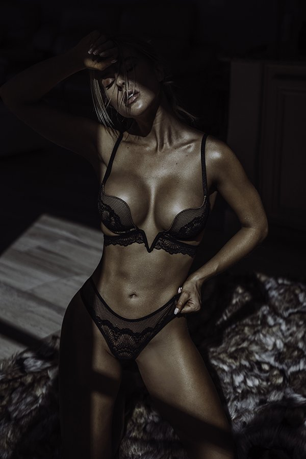 tanned model posing with black lingerie