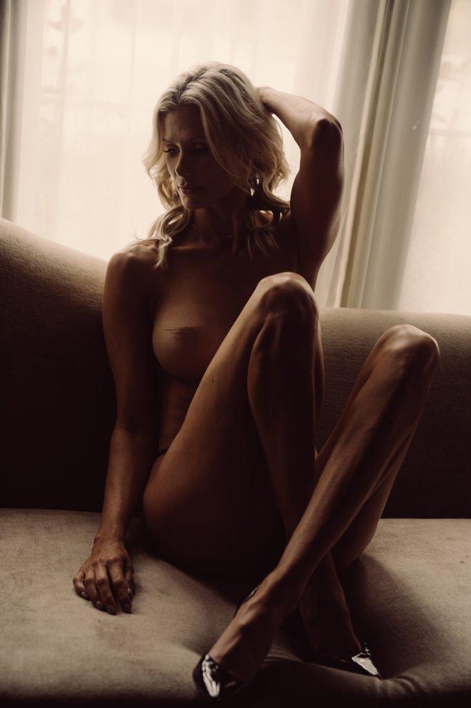 woman with folded knees sitting on velvet couch - boudoir thousand oaks