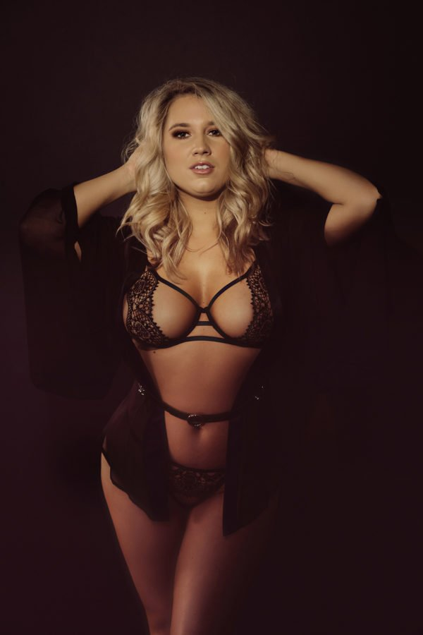 Curvy blonde model poses with hands on her head
