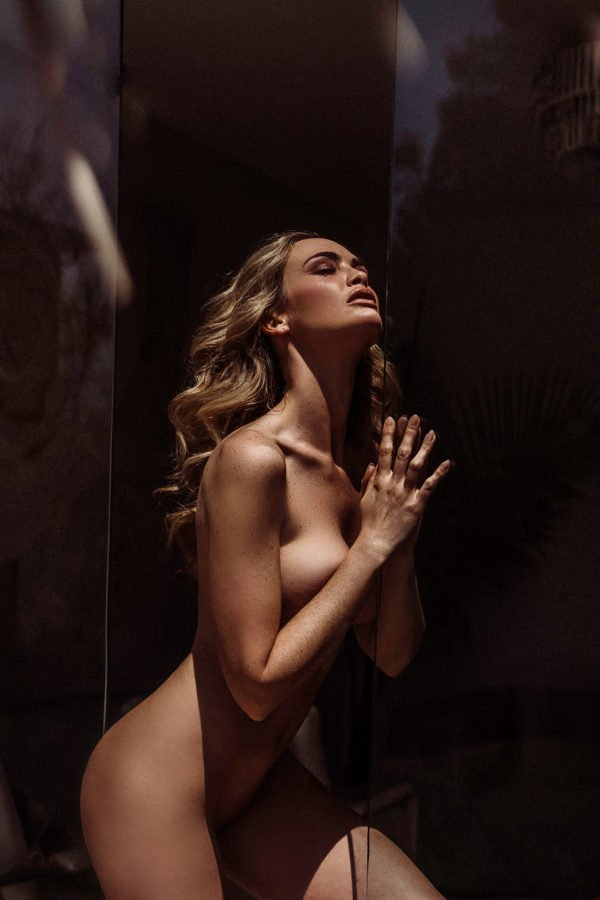 implied nude photo of blonde woman by glass panels