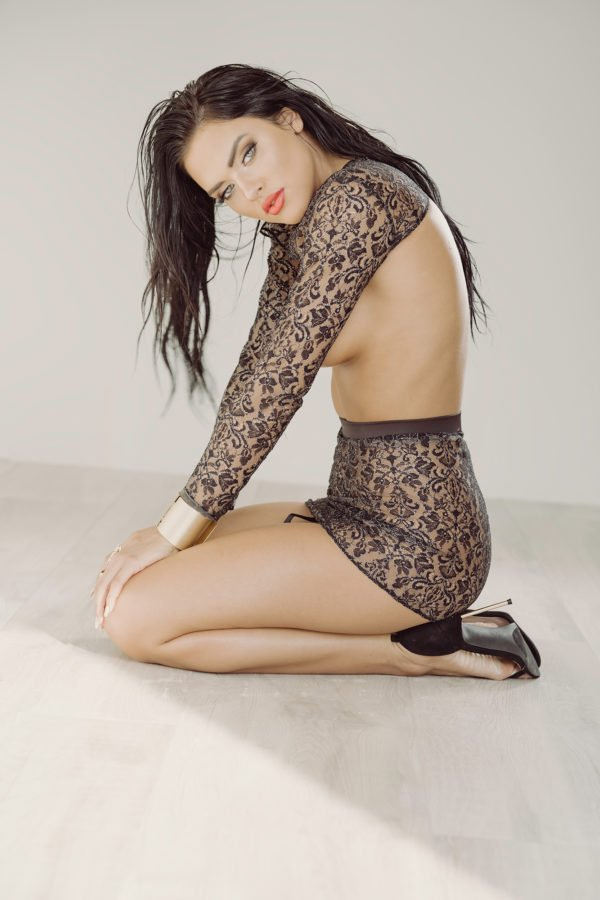 Kelsy Smeby sitting on the floor in a two piece mesh black outfit