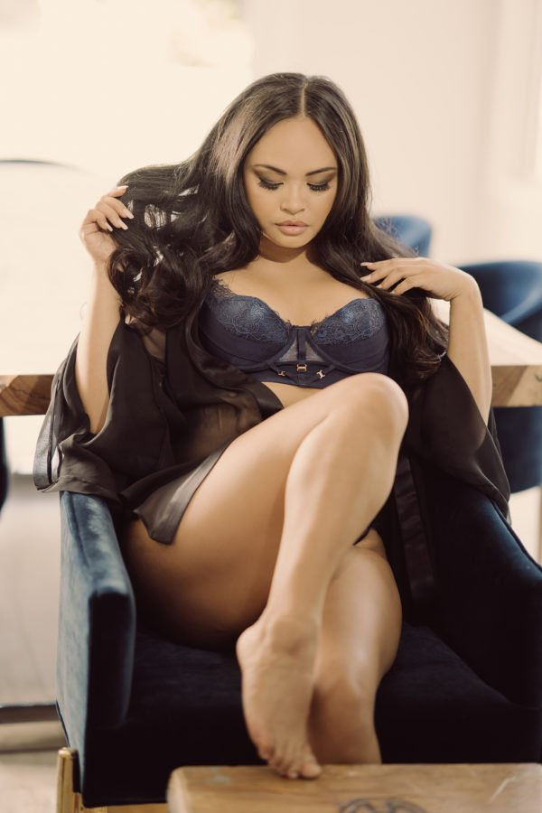 brunette woman in navy Bordelle lingerie in a velvet chair