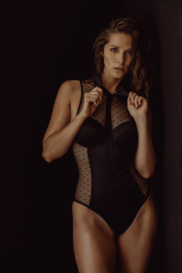 oily woman in black polka dot collard bodysuit posing