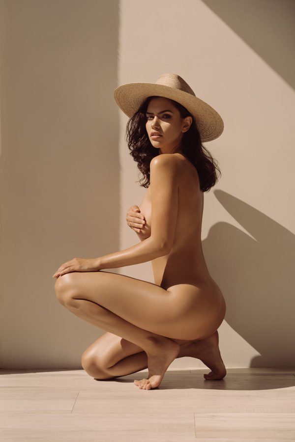 nude model with wide brim hat posing on one knee