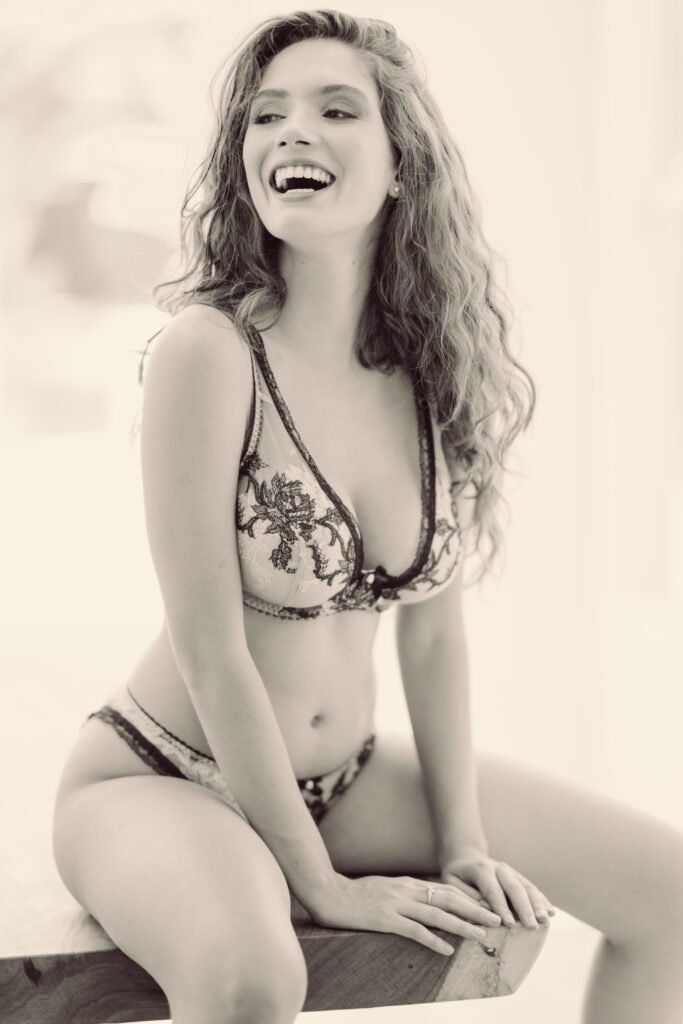 Bianca Rodrigues Grimes wearing Agent Provocateur lingerie smiling in a black and white boudoir photo